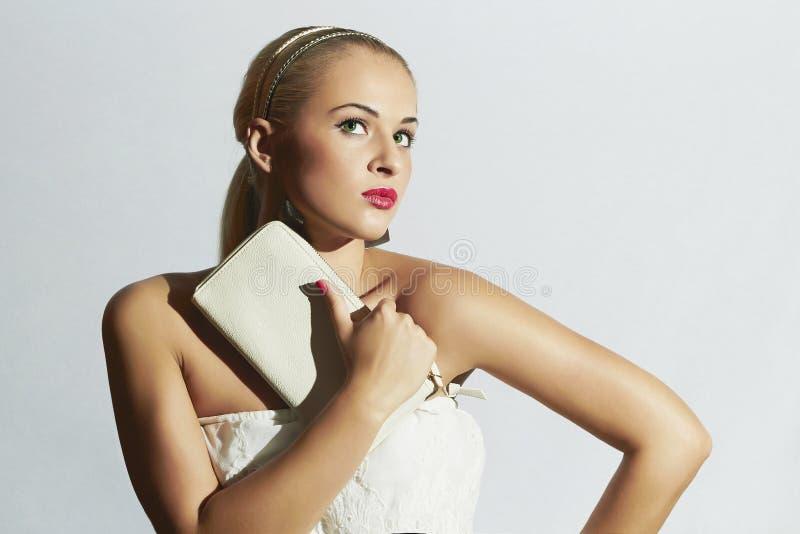 Mulher loura bonita no vestido branco Menina à moda da forma com embreagem branca Bordos vermelhos Noiva fotografia de stock royalty free