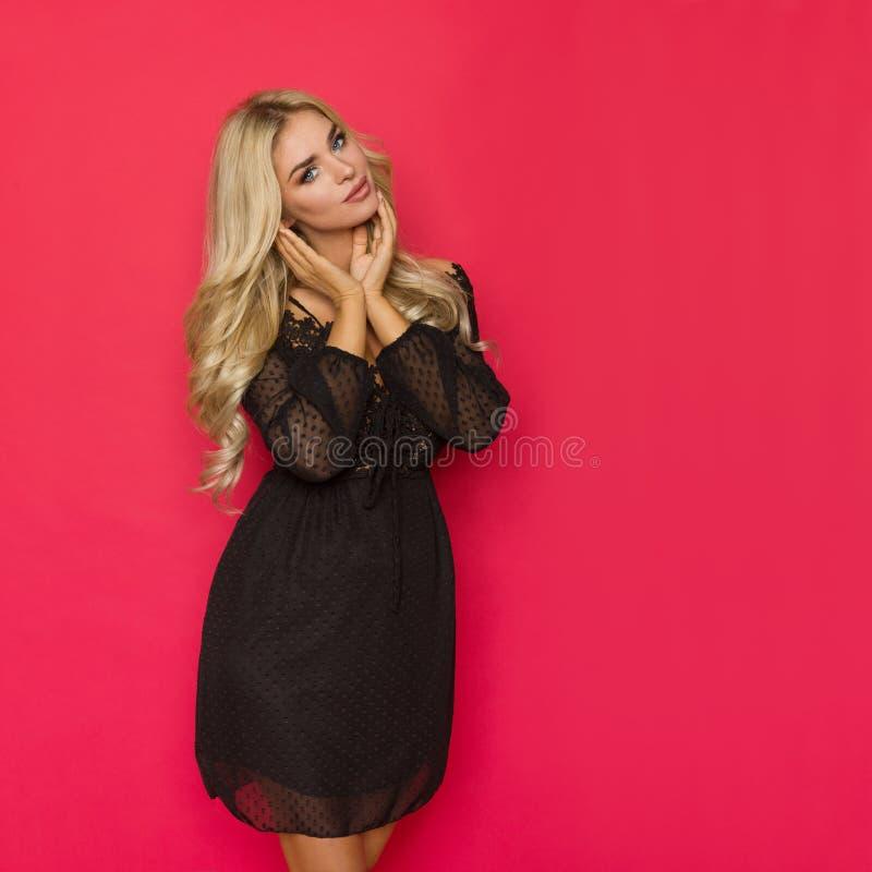 A mulher loura bonita no vestido preto do laço está guardando a cabeça nas mãos fotografia de stock royalty free