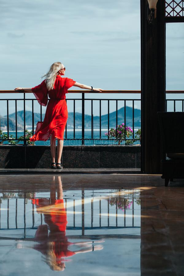 Mulher loura bonita no vestido vermelho com vidros no balcão Reflexão no assoalho na perspectiva do mar imagem de stock