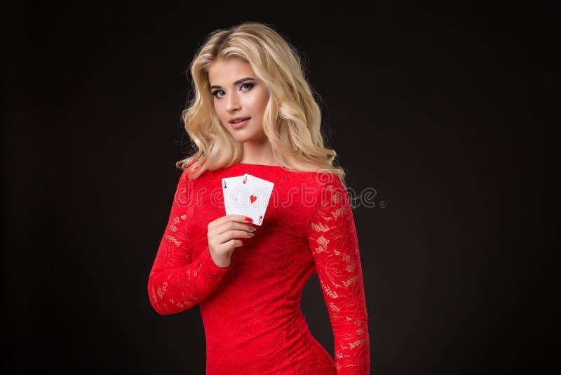 Mulher loura bonita nova com os cartões de jogo sobre o preto poker foto de stock royalty free