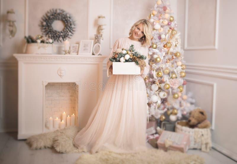 A mulher loura bonita nova decora os brinquedos da árvore de Natal fotos de stock royalty free
