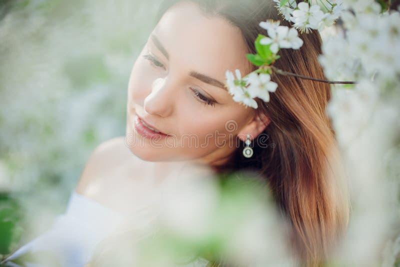 A mulher loura bonita nova em amêndoas de florescência jardina imagens de stock royalty free