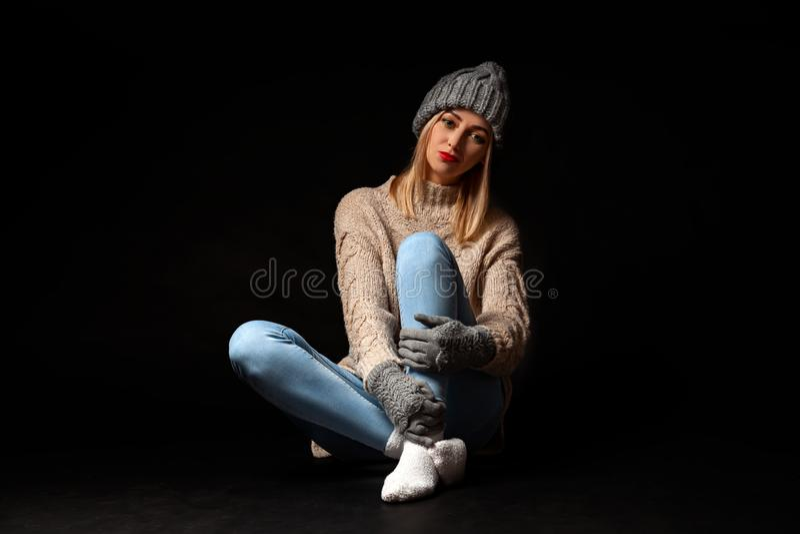 A mulher loura bonita nova em luvas e no chapéu feitos malha no cinza, calças de ganga, camiseta bege senta-se no assoalho com pé fotografia de stock