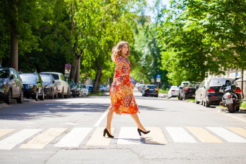 A mulher loura bonita nova em um vestido vermelho da flor cruza a estrada em uma faixa de travessia imagem de stock