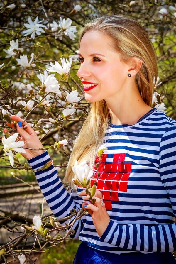 Mulher loura bonita nova no jardim de florescência da magnólia Menina de sorriso com flores da magnólia imagem de stock royalty free