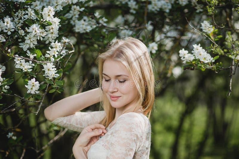 Mulher loura bonita nova no jardim de florescência A menina delicada aprecia a natureza da mola imagem de stock royalty free