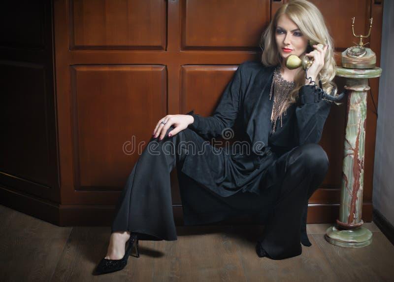 Mulher loura bonita nova no terno preto elegante que fala pelo assento do telefone relaxado no assoalho Menina justa sedutor do c imagem de stock
