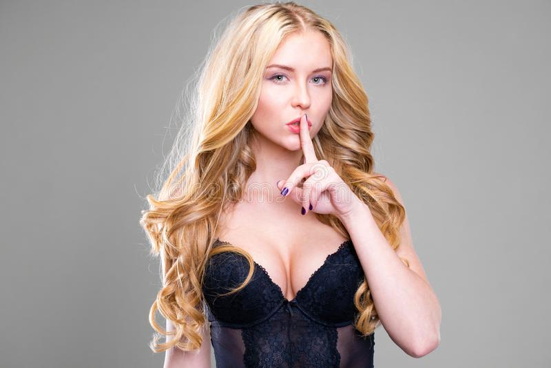 A mulher loura bonita nova pôs o dedo indicador aos bordos como o sinal do silêncio imagem de stock royalty free