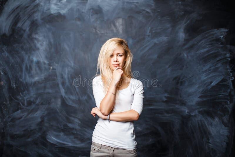 A mulher loura bonita nova pensa em um fundo o blackboar fotografia de stock royalty free