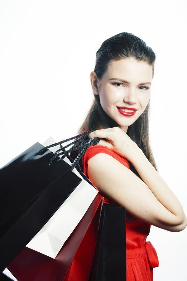 Mulher loura bonita nova que levanta alegre isolado no fundo branco com os sacos na venda do Natal em dres vermelhos imagens de stock