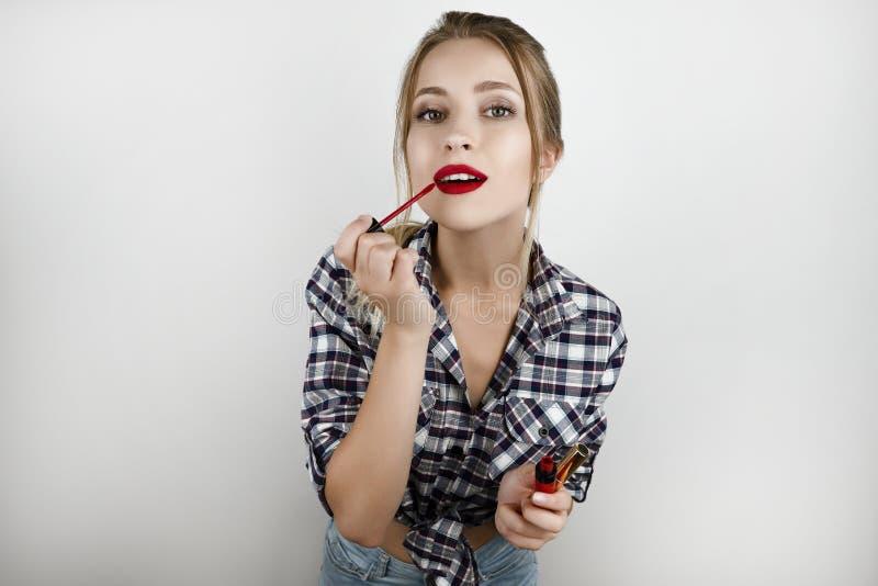 A mulher loura bonita nova que veste o short quadriculado na moda da camisa e da sarja de Nimes que aplica o batom vermelho isolo fotografia de stock