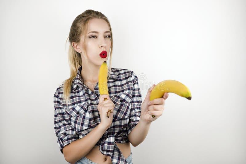 Mulher loura bonita nova que veste o short quadriculado na moda da camisa e da sarja de Nimes que mantém duas bananas como armas  fotografia de stock