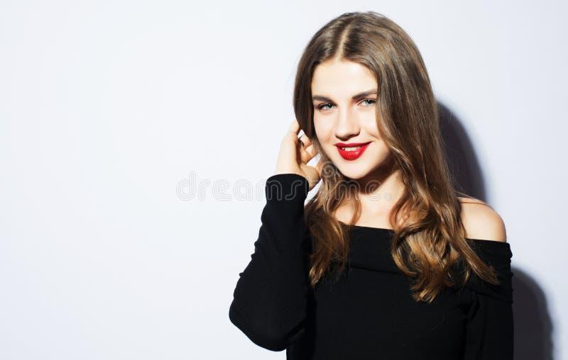 Mulher loura bonita nova que veste o vestido preto que levanta sobre o fundo branco imagens de stock