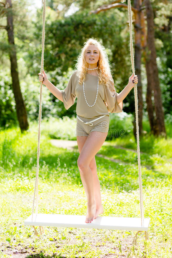 Mulher loura bonita que balança no balanço da corda fotografia de stock royalty free