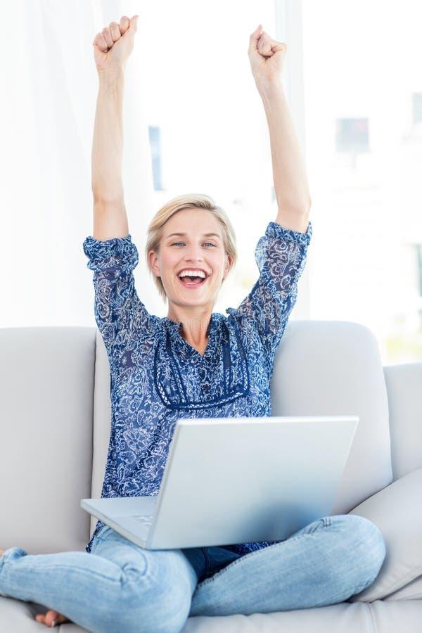 Mulher loura bonita que cheering no sofá imagem de stock royalty free