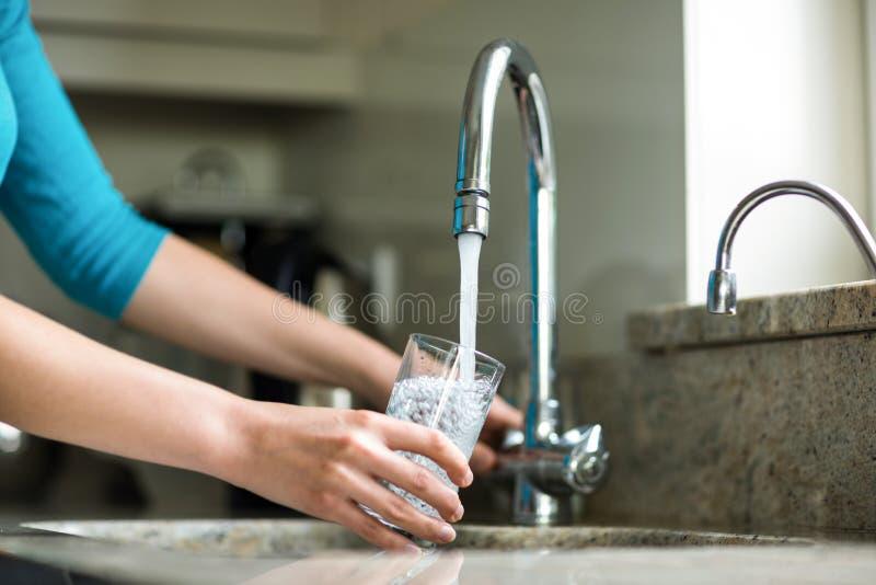 Mulher loura bonita que enche um vidro da água imagens de stock