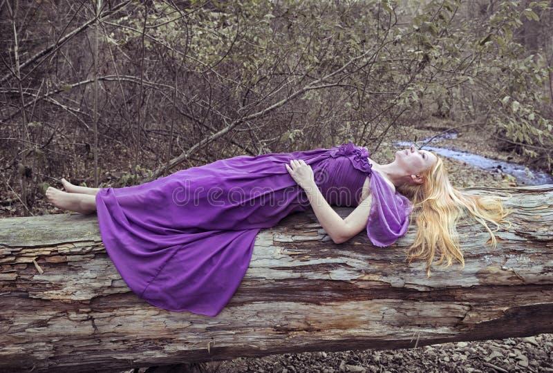 Mulher loura bonita que encontra-se na árvore pelo rio fotografia de stock royalty free