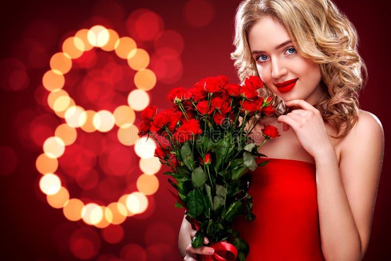 Mulher loura bonita que guarda o ramalhete de rosas vermelhas no fundo do bokeh Dia internacional do ` s das mulheres, oito março imagens de stock