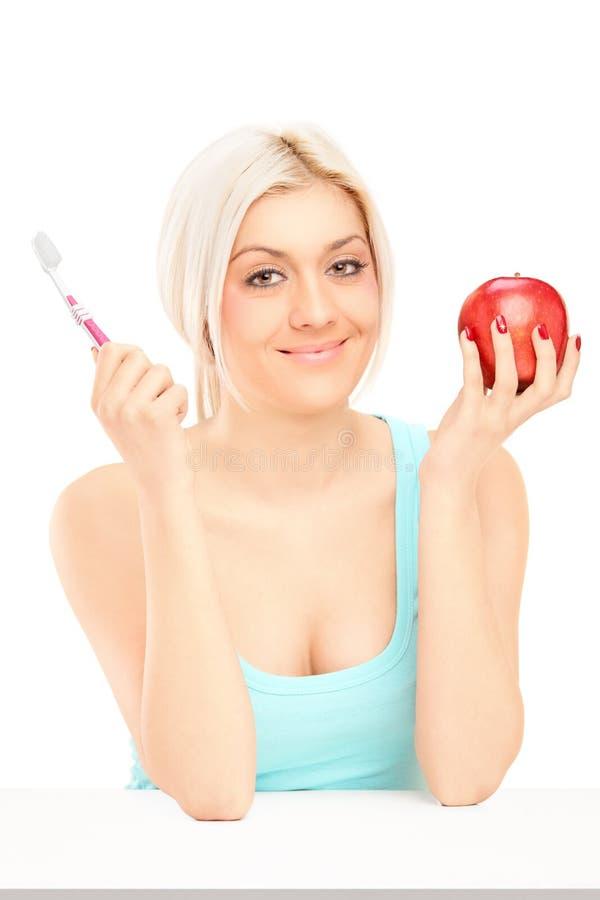 Mulher loura bonita que guardara a maçã e a escova de dentes vermelhas imagens de stock