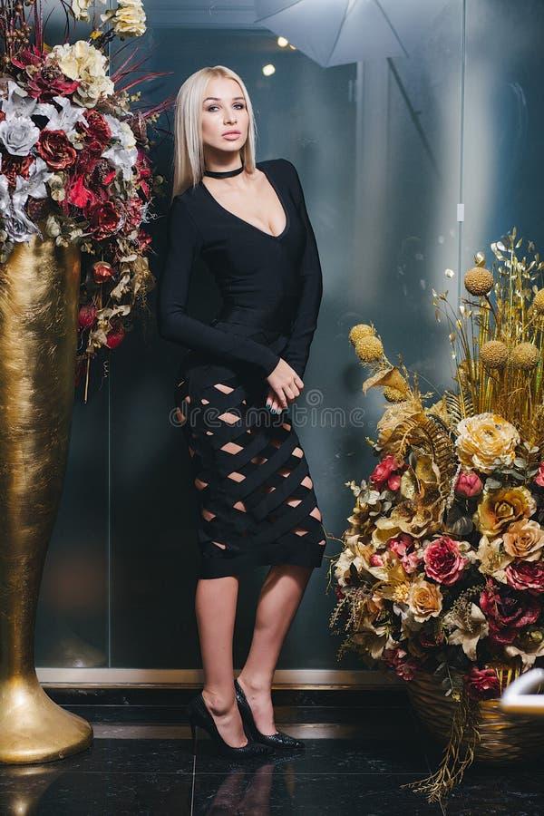Mulher loura bonita que levanta no vestido preto fotos de stock royalty free