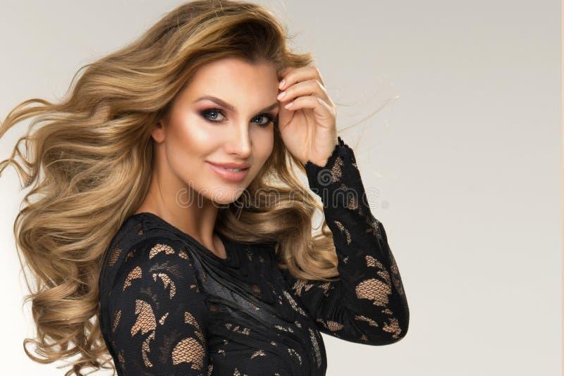Mulher loura bonita que levanta no vestido preto Menina com cabelo curly longo imagens de stock royalty free