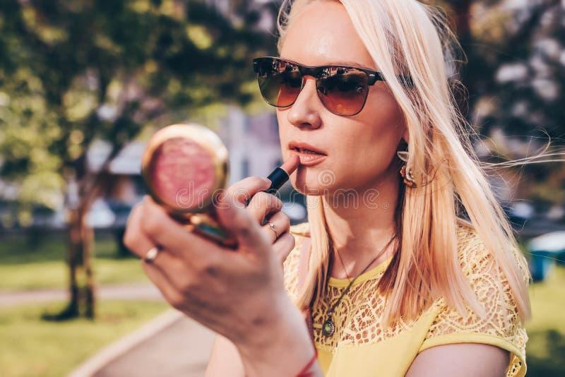 A mulher loura bonita que olha em um pequeno espelha e corrige o batom na rua fotos de stock