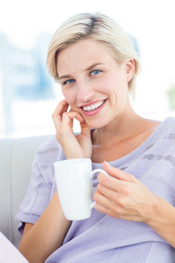 Mulher loura bonita que senta-se no sofá e que guarda uma caneca fotos de stock