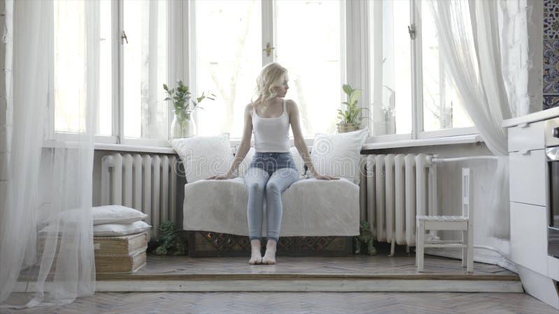 Mulher loura bonita que senta-se no sofá pequeno branco em casa na frente da janela a??o Menina atrativa no tanque branco fotos de stock royalty free