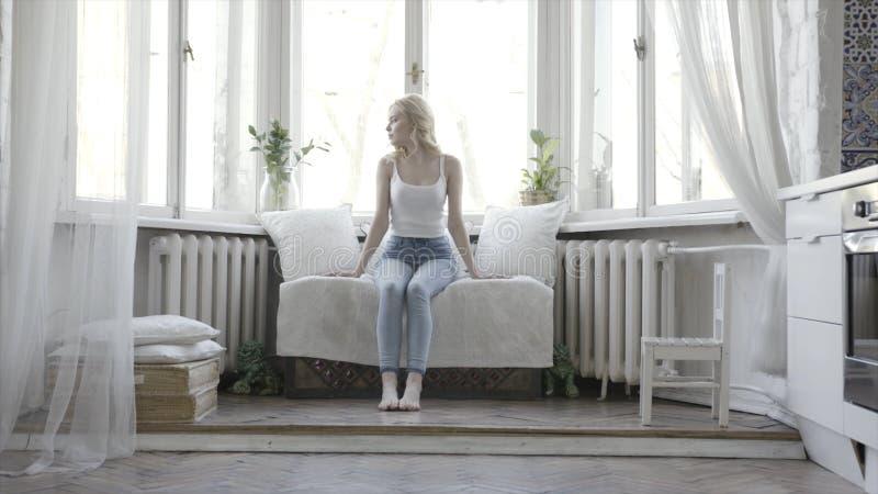 Mulher loura bonita que senta-se no sofá pequeno branco em casa na frente da janela a??o Menina atrativa no tanque branco imagens de stock royalty free