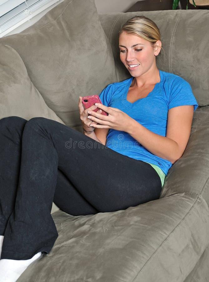 Mulher loura bonita que usa o smartphone no sofá imagens de stock royalty free