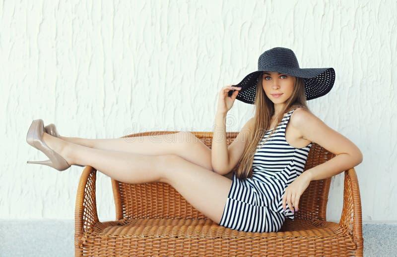 Mulher loura bonita que veste um vestido listrado, chapéu de palha preto fotos de stock