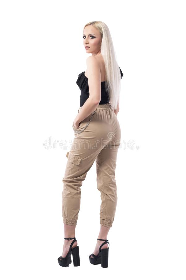 Mulher loura bonita séria com mãos em uns bolsos que olham a câmera sobre o ombro foto de stock