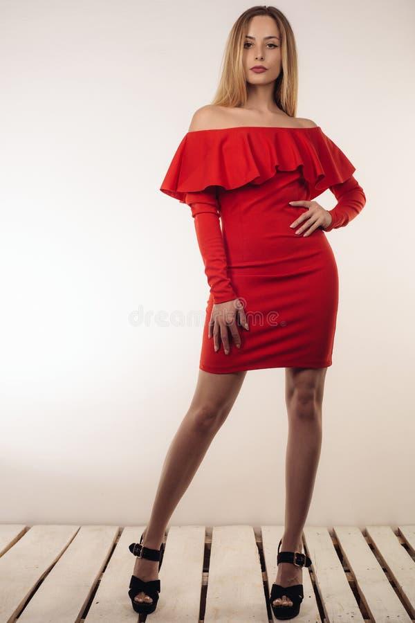 Mulher loura bonita sensual que levanta no vestido vermelho que levanta perto de uma parede branca fotografia de stock