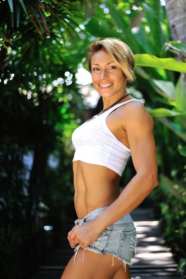 Mulher loura bonita 'sexy' que levanta em calças de brim curtos Menina com por imagens de stock royalty free