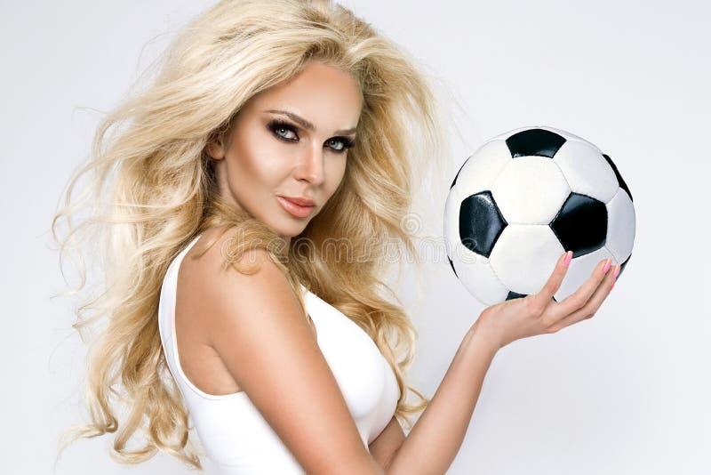 A mulher loura bonita, 'sexy' vestiu-se na roupa dos esportes, jogo no futebol imagem de stock