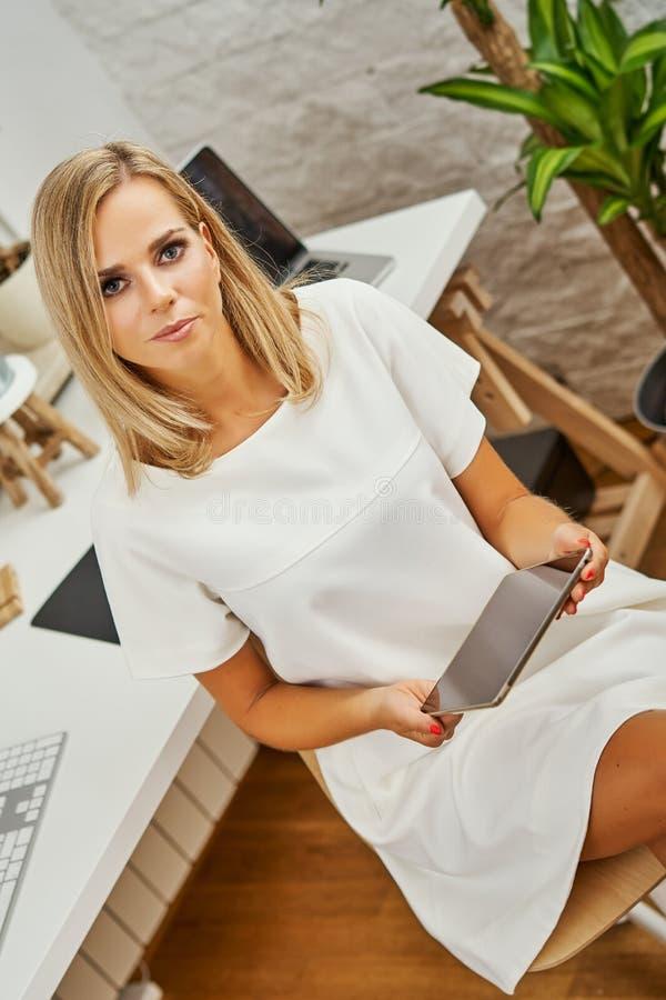 A mulher loura bonita trabalha na tabuleta no escritório imagem de stock royalty free