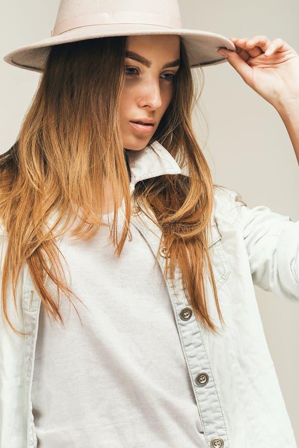 Mulher loura bonito atrativa na camisa e no chapéu da sarja de Nimes foto de stock