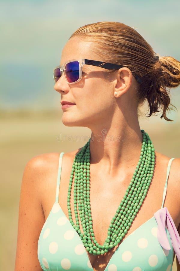 Mulher loura bronzeada bonita no banho de sol da praia fotografia de stock royalty free