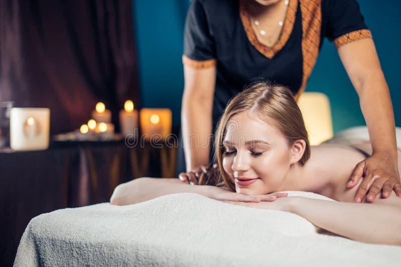 Mulher loura calma nova que aprecia a massagem completa do corpo no centro dos termas fotografia de stock royalty free
