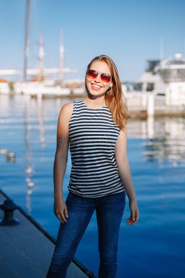 A mulher loura caucasiano com pele bronzeada listrou o t-shirt e a calças de ganga pelo litoral lakeshore, com os barcos dos iate foto de stock
