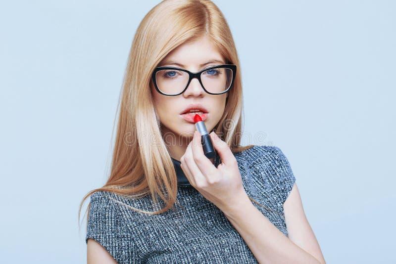 Mulher loura caucasiano esperta nova que aplica o cinemat vermelho do batom foto de stock