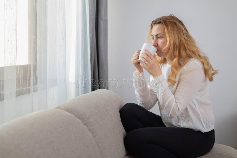 Mulher loura caucasiano que senta-se em um sofá que bebe seu café da manhã na frente de uma janela, ocasional e relaxado imagem de stock royalty free