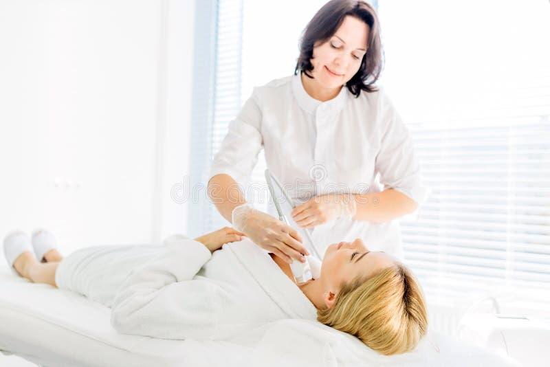 A mulher loura com cabelo longo faz o laser da cara que resurfacing no centro da beleza foto de stock