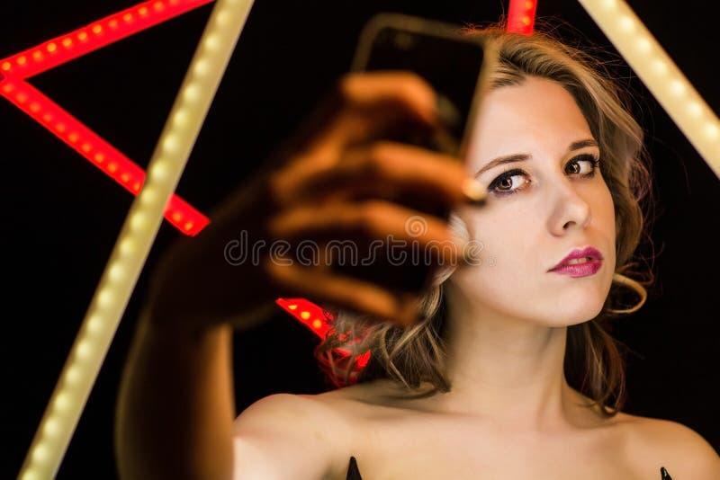 A mulher loura com composição e denominação faz o selfie fotografia de stock royalty free