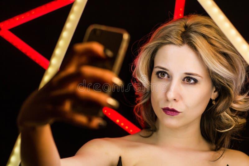A mulher loura com composição e denominação faz o selfie foto de stock royalty free