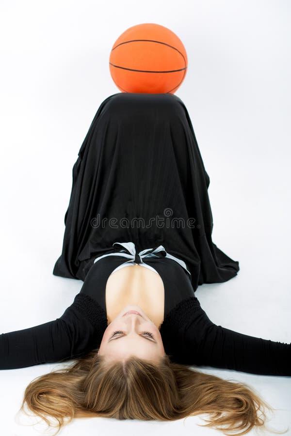 Mulher loura com a esfera do basquetebol que encontra-se no assoalho fotografia de stock