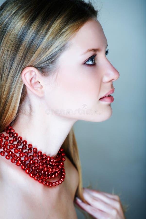 Mulher loura com grânulos vermelhos fotos de stock royalty free