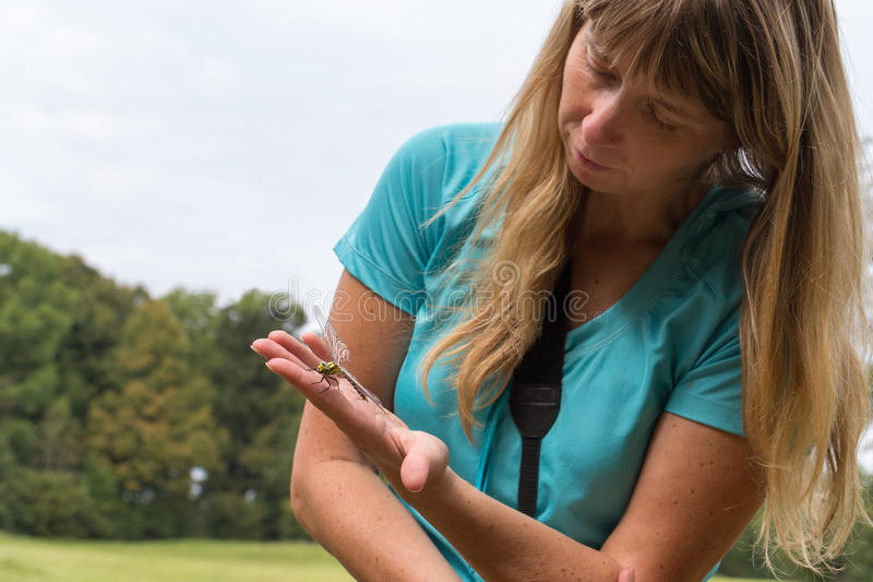 Mulher loura com a libélula em sua mão fotos de stock