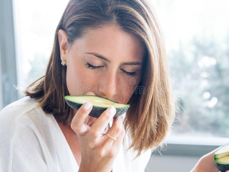 Mulher loura com os olhos verdes na peça moderna da cozinha um abacate a jogar com colocação dele sobre os olhos e a cabeça foto de stock royalty free