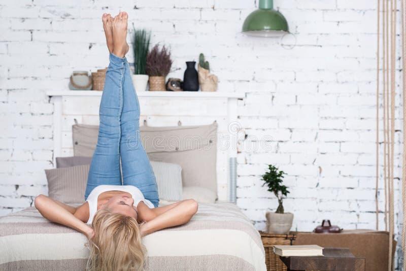 Mulher loura com pés acima na cama imagens de stock royalty free